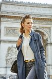 Woman near Arc de Triomphe in Paris, France looking aside. Stylish autumn in Paris. young woman in trench coat near Arc de Triomphe in Paris, France looking Stock Images