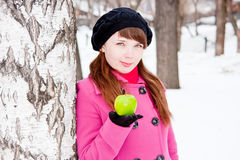 Woman  near a birch with a green apple in hands Royalty Free Stock Photography