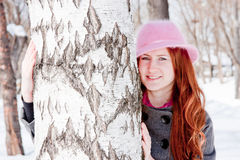 Woman near a birch in winter in a park Royalty Free Stock Image
