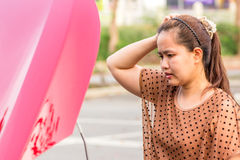 Woman near broken car needs assistance. Woman near broken car needs assistance looking under opened hood Royalty Free Stock Photography