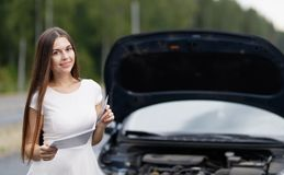 Woman in front of her car broken car Stock Image