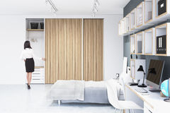 Woman near a built in wardrobe in a room. Rear view of a woman standing near a built in wooden wardrobe in a room with a double bed and a number of bookshelves Stock Image