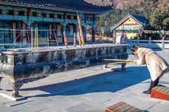 Woman near the censer with is holding a burning joss aroma incense sticks or candles and worships in Hua-Yang temple in royalty free stock images