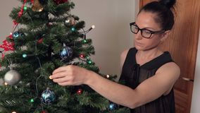 Woman near Christmas tree with Christmas decoration. In room stock footage