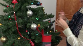 Woman near Christmas tree with Christmas decoration. In room stock video footage
