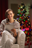 Woman near Christmas tree holding tablet PC