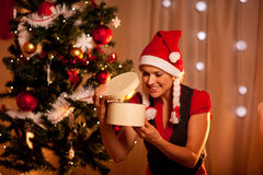 Woman near Christmas tree looking inside gift Royalty Free Stock Images