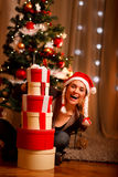 Woman near Christmas tree looking out from gifts Royalty Free Stock Photography