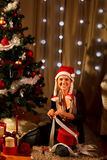 Woman near Christmas tree making gift Royalty Free Stock Photography