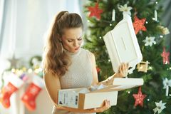Woman near Christmas tree pulling out broken dish from parcel. Sad modern woman near Christmas tree pulling out a broken dish from the parcel royalty free stock photography