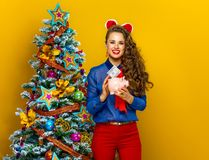 Woman near Christmas tree putting dollar bill in piggy bank Stock Images