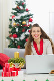 Woman near Christmas tree sending greeting emails Stock Image