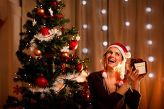 Woman near Christmas tree shaking present Royalty Free Stock Image