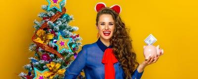 Woman near Christmas tree showing piggy bank with a dollar bill. Festive season. smiling stylish woman near Christmas tree on yellow background showing a piggy stock photos