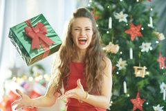 Woman near Christmas tree throwing up green Christmas gift. Smiling stylish woman in red dress near Christmas tree throwing up green Christmas present box stock photos