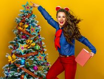 Woman near Christmas tree on yellow background with book Stock Photography
