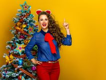 Woman near Christmas tree on yellow background got an idea Stock Photo