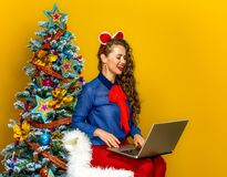 Woman near Christmas tree on yellow background using laptop Stock Photography