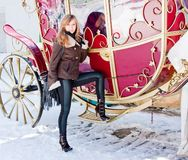Woman near a coach in a winter park. Young beautiful woman near a coach in a winter park Stock Photography