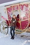 Woman near a coach in a winter park Royalty Free Stock Images