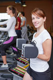 Woman near crosstrainer lifting. Happy women near a crosstrainer lifting weights in a fitness center Stock Image