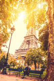 Woman near Eiffel tower in fall. Middle age, pretty woman near Eiffel tower in sunny fall park Royalty Free Stock Images