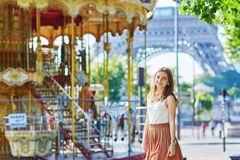 Woman near the Eiffel tower and merry-go-round Royalty Free Stock Image