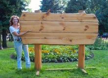 Woman near empty wooden billboard Stock Photography