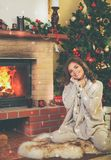 Woman near fireplace in Christmas decorated house.  Royalty Free Stock Image