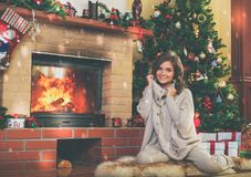 Woman near fireplace in Christmas decorated house.  Stock Photography