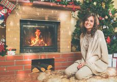 Woman near fireplace in Christmas decorated house.  Stock Photo