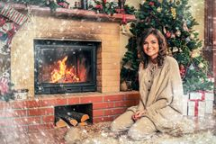 Woman near fireplace in Christmas decorated house Royalty Free Stock Photos