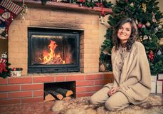 Woman near fireplace in Christmas decorated house Stock Image