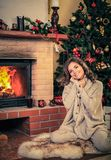 Woman near fireplace in Christmas decorated house Stock Photography