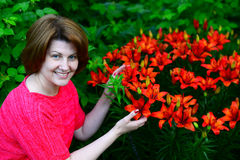 Woman near flower bed with orange lilies Royalty Free Stock Photos