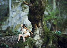 Woman near giant tree trunk in woods. Young beautiful woman sitting on roots of  old giant tree in forest Royalty Free Stock Photography
