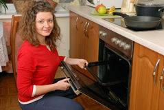 Woman near kitchen oven Royalty Free Stock Image