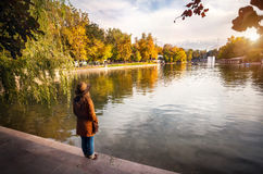 Woman near the lake at autumn park Stock Photo