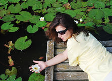 Woman near the lake with water lilies. Stock Photos