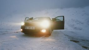 Woman near lonely parked car in snow deserted area problem with tire. Mummelsee, Germany - Circa 2019: Woman lonely parked Skoda Octavia brown car in snowy storm stock video footage