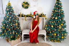 Woman near x-mas tree. Beautiful woman in evening dress, young lady female near big x-mas fir-tree trees, happy New Year party golden decorations, accessory Royalty Free Stock Image