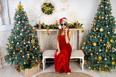Woman near x-mas tree. Beautiful woman in evening dress, young lady female near big x-mas fir-tree trees, happy New Year party golden decorations, accessory Stock Photography