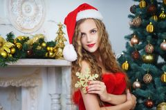 Woman near x-mas tree. Beautiful woman in evening dress, young lady female near big x-mas fir-tree trees, happy New Year party. Sexy santa girl, dreaming about Royalty Free Stock Images