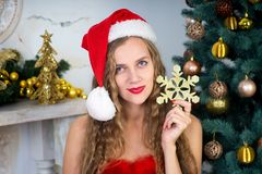Woman near x-mas tree. Beautiful woman in evening dress, young lady female near big x-mas fir-tree trees, happy New Year party. Sexy santa girl, dreaming about Royalty Free Stock Photo