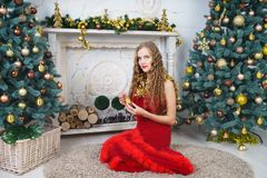 Woman near x-mas tree. Beautiful woman in evening dress, young lady female near big x-mas fir-tree trees, happy New Year party. Sexy santa girl, dreaming about Stock Photos