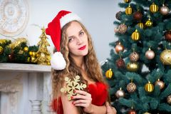 Woman near x-mas tree. Beautiful woman in evening dress, young lady female near big x-mas fir-tree trees, happy New Year party. Sexy santa girl, dreaming about Royalty Free Stock Photography