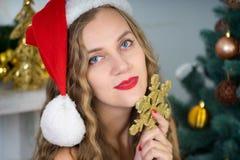 Woman near x-mas tree. Beautiful woman holds gold snowflake, young lady female near big x-mas fir-tree tree, happy New Year party. Sexy santa girl, dreaming Stock Photos
