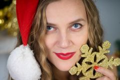 Woman near x-mas tree. Beautiful woman holds gold snowflake, young lady female near big x-mas fir-tree tree, happy New Year party. Sexy santa girl, dreaming Stock Image