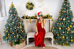 Woman near x-mas tree. Beautiful woman in evening dress, young lady female near big x-mas fir-tree trees, happy New Year party golden decorations, accessory Royalty Free Stock Photography