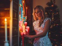 Woman near a new-year tree with gifts and candles stock images